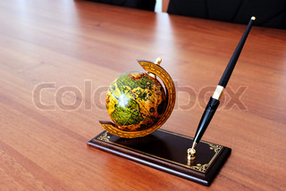 globe and pen on prop over brown office desk