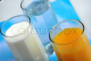 three glasses with water, milk and juice closeup