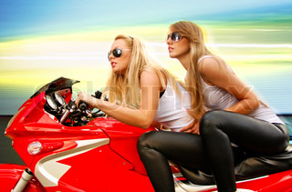 two pretty blonde woman on a big red motorcycle