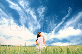 Young beauty pregnant woman in the field