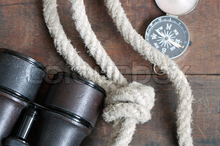 Still life with antique binoculars, rope and compass on wooden background