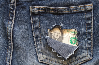 One dollar note inside hole in old jeans pocket