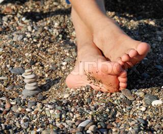 child feet next to rocks stack on beach