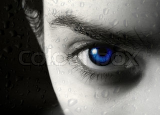 Photo of half of face of the beautiful young blue-eyed girl and drop of a rain on glass