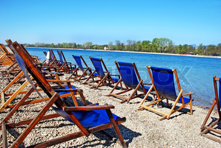 row of  folding chairs by on beach by blue water