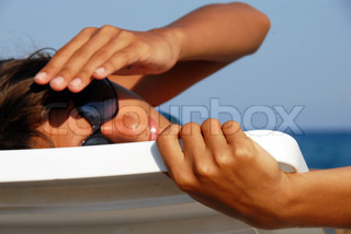 young girl in sunglasses turned in plastic chair lying on beach