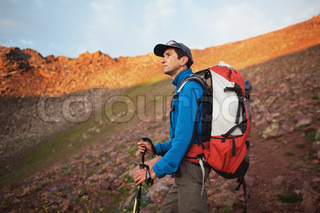 Backpacker in morning mountains awaiting the sunrise
