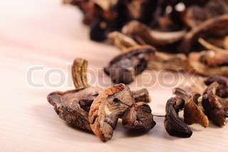 Dried mushrooms in heap on wooden table