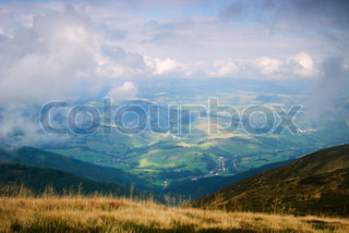 Beautiful blue sky and dry grass and view on the village in Carpathian mountains