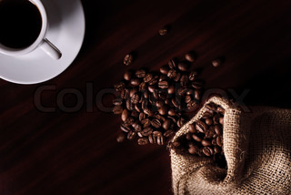 Coffee still life with cup, coffee beans in bag. Low key light.