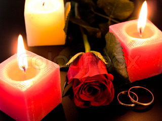 wedding golden rings, rose and candles in the night