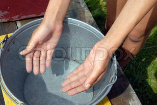 hands in clean cold transparent well water in metal bucket