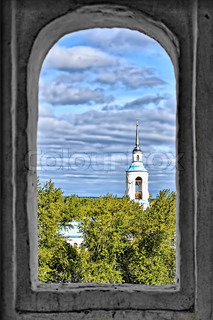 A white bell tower of the Transfiguration Cathedral with buildings against the blue sky, clouds, and yellow-green trees from the window opening a stone tower (St. Nicholas Monastery, the Verhoturie Sverdlovsk region)