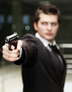 A bussiness man with a gun. (The focus is on the hand and gun)