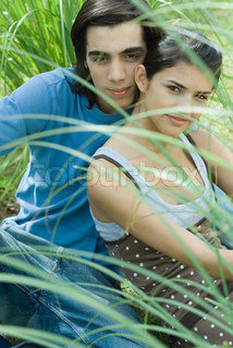 ?Odilon Dimier/AltoPress/Maxppp ; Young couple sitting in grass, looking at camera