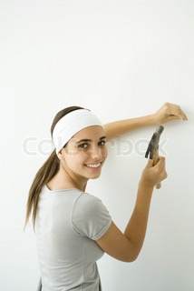 ?Alix Minde/AltoPress/Maxppp ; Teen girl hammering nail into wall, smiling over her shoulder at camera