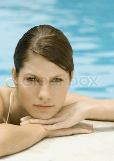 Young woman resting head on side of pool