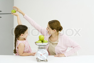 Woman and girl, girl holding up apple, woman reaching for it