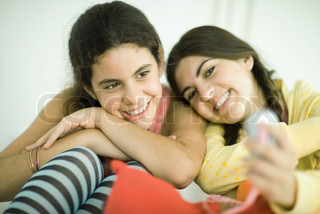 Two young female friends, one holding out cell phone