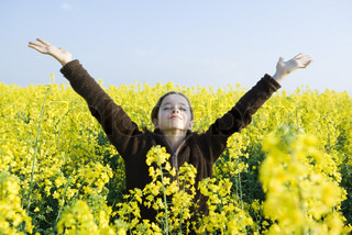 Girl standing in field of canola in bloom, head back, eyes closed and arms raised