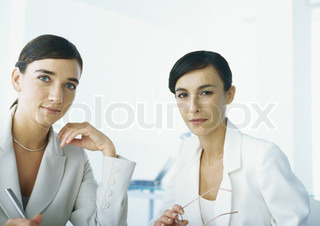 Two businesswomen looking at camera, head and shoulders