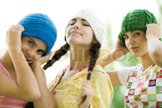 Young female friends wearing knit hats, looking at camera