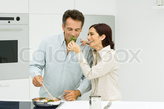 Man cooking, woman holding up basil for man to smell