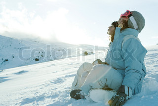 Teen girls sitting in snow with heads back and eyes closed