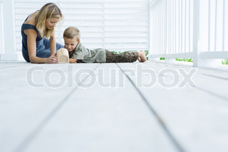 Mother and son sitting on floor of porch looking at birdhouse