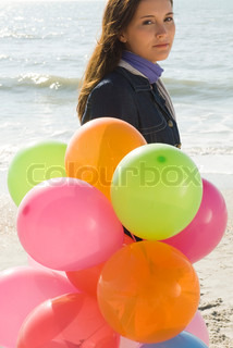 Preteen girl with bunch of balloons walking on beach
