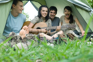 Friends in tent together, teen girl playing guitar
