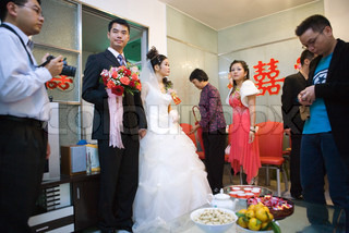 Chinese wedding, bride and groom standing, food and drink on table