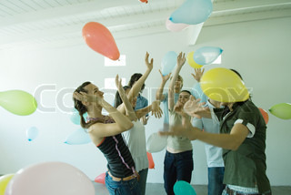 Group of young friends hitting balloons floating in the air