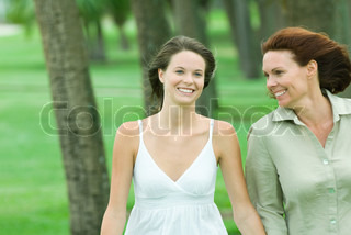 Mother and teenage daughter walking together outdoors, both smiling