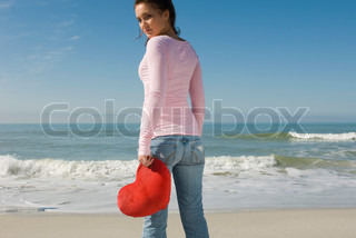 Preteen girl at beach holding stuffed heart-shaped toy, looking over shoulder at camera
