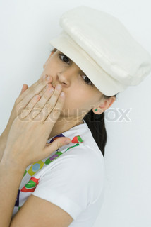 Teenage girl covering mouth with hands, looking at camera, portrait