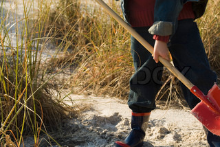 Boy digging with shovel in sand