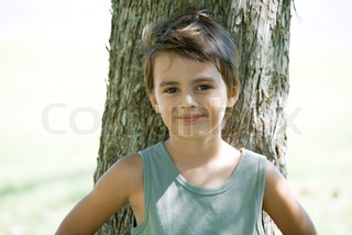 Little boy outdoors, leaning against tree trunk, smiling at camera