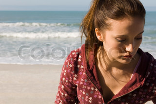 Preteen girl at beach contemplatively looking down