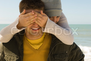 Young couple enjoying winter's day outing to beach, girl surprising boyfriend from behind