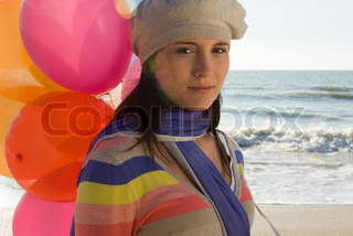 Preteen girl with bunch of balloons at beach
