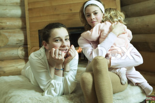 Two teen girls with little sister, smiling at camera