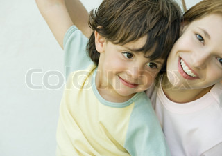 Brother and sister having fun, arms raised, close-up
