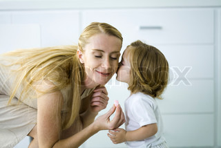Little girl kissing mother's cheek, woman holding a tiny heart, eyes closed