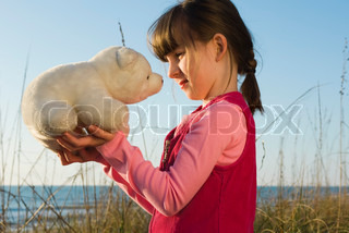 Young girl face to face with stuffed toy polar bear cub