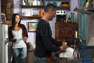Couple in kitchen, husband doing dishes