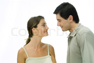 Young couple face to face, smiling at each other, portrait