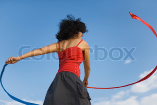 Young woman spinning around with ribbons outdoors