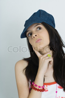 Teenage girl with finger on cheek, looking up, portrait