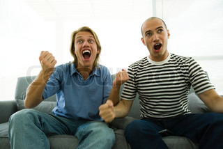Two men sitting on sofa watching TV, cheering with clenched fists